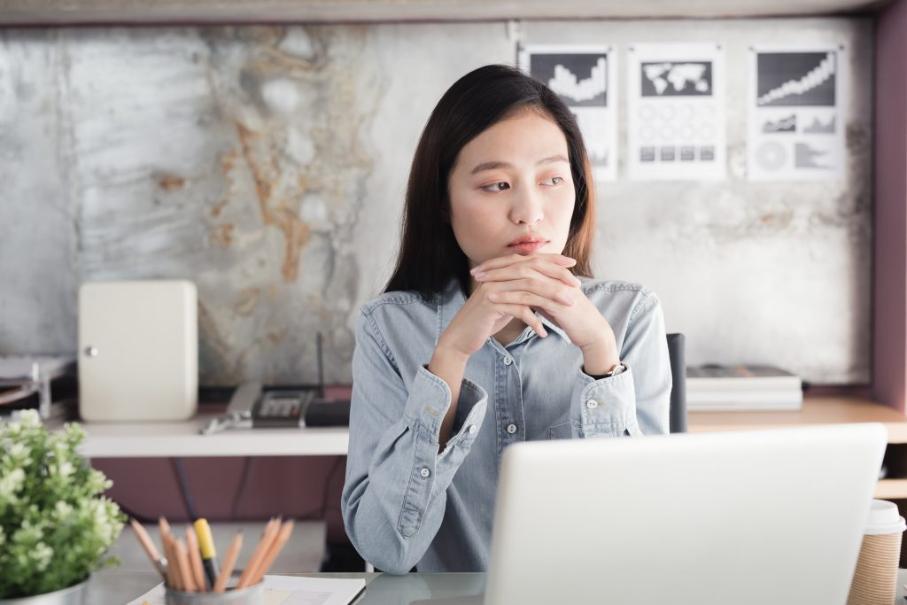 A depressed woman is distracted at work sitting at her desk with a laptop