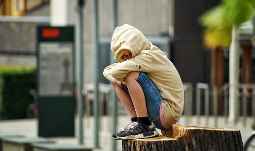 A sad, young boy sitting outside with a hoodie on