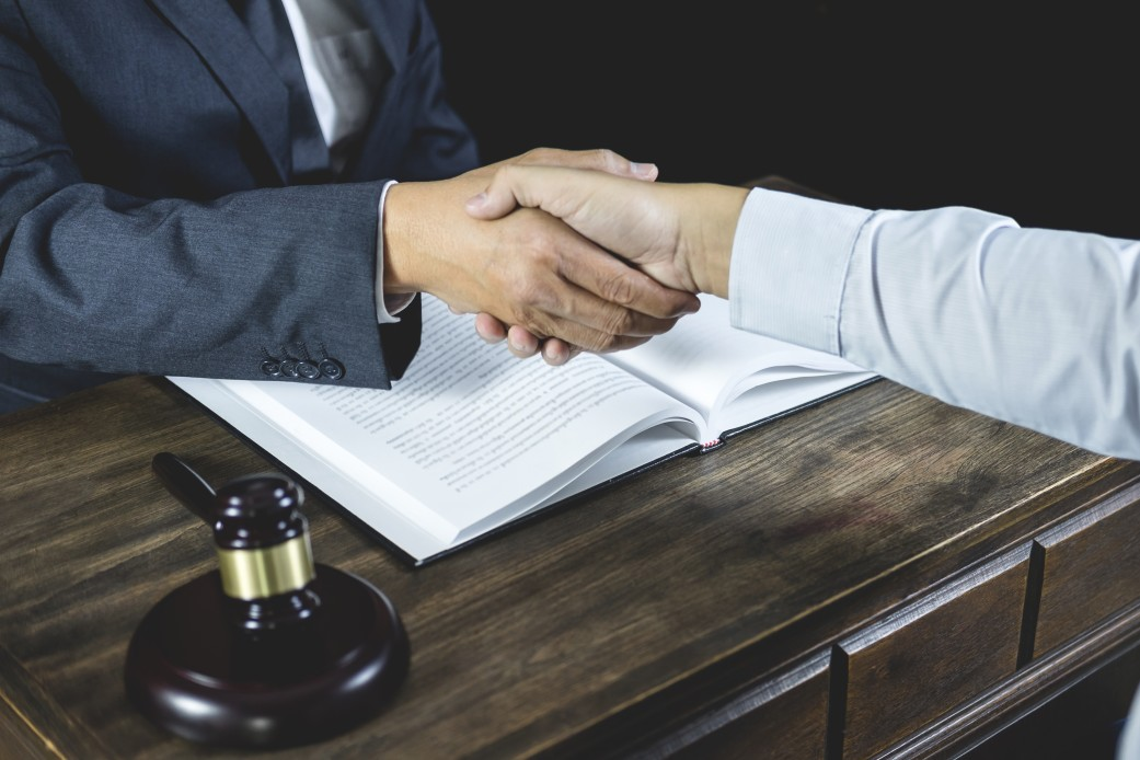 A lawyer shaking a client's hand over a desk in an office