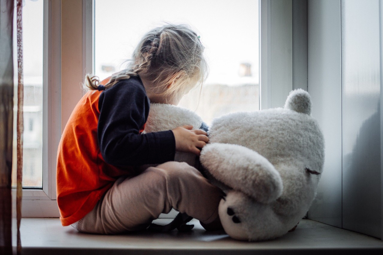A sad girl sits by a window with a teddy bear