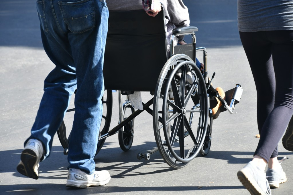 A man pushing an injured victim in a wheelchair